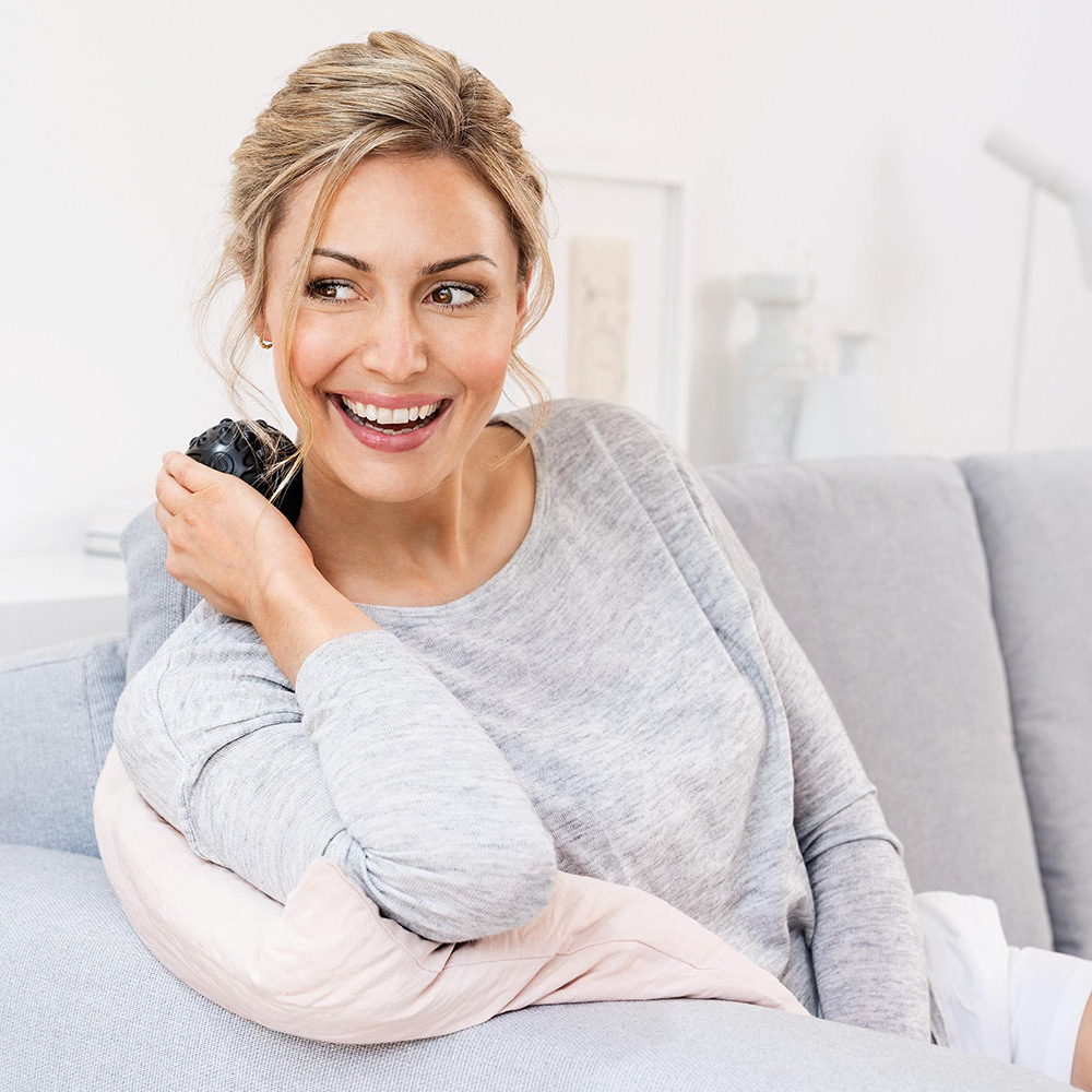schwarzer Massageball mit Vibration im Nacken einer Frau